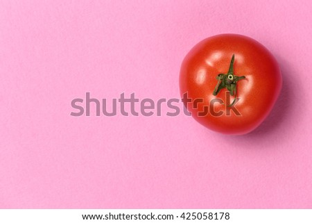 Top view of a ripe juicy tomato on a pink background. Fresh tomato. Beautiful tomatoes with a leaf. Tomato in the top right corner of the composition. Tomato wallpaper. Vegetable texture - stock photo