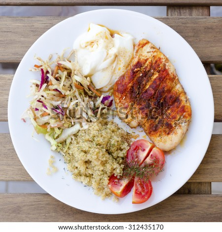 Top view of a roasted in the oven chicken breast fillet garnished with paprika served in a plate with cabbage and carrot salad, quinoa, yogurt and tomatoes on wooden table. A healthy meal. - stock photo