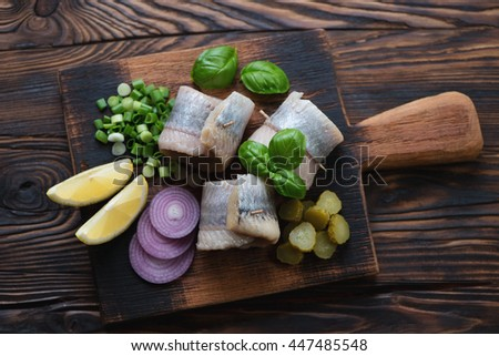 Top view of a rustic wooden serving board with herring rolls