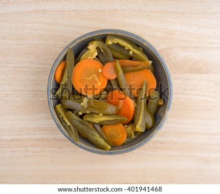 Top view of a serving of canned sliced jalapeno peppers with carrots in an old bowl atop a wood table top. - stock photo