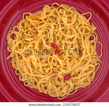 Top view of a serving of Chow Mein noodles with pieces of shrimp on a bright plate.