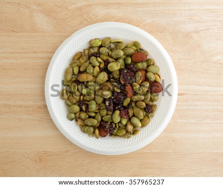 Top view of a serving of dry roasted edamame with dried cranberries and blueberries plus almonds and pumpkin seeds on a white foam plate atop a wood table top illuminated with window light.