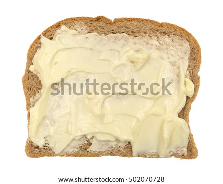 Top view of a slice of wheat bread with mayonnaise and margarine isolated on a white background.