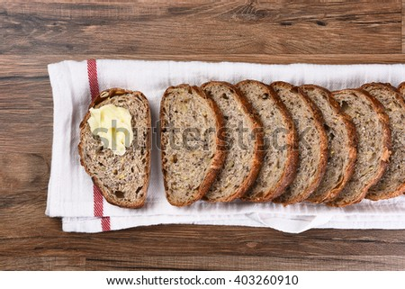 Top view of a sliced loaf of multi-grain bread on a towel, one slice is buttered. - stock photo