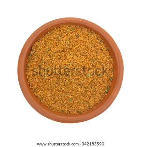 Top view of a small bowl filled with dry chipotle pepper marinade ingredients isolated on a white background.