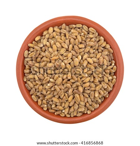 Top view of a small bowl filled with red winter wheat berries isolated on a white background. - stock photo