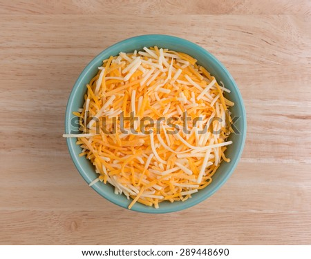 Top view of a small bowl filled with shredded white cheddar, sharp cheddar and mild cheddar cheeses atop a wood table top. - stock photo