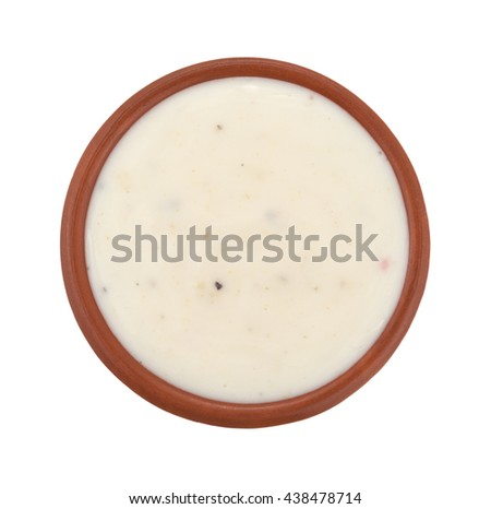 Top view of a small bowl of creamy Italian salad dressing isolated on a white background.
