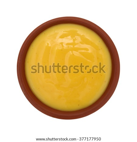 Top view of a small bowl of honey mustard salad dressing isolated on a white background.