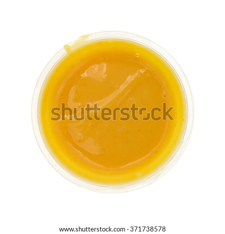 Top view of a small container of honey mustard salad dressing isolated on a white background. - stock photo