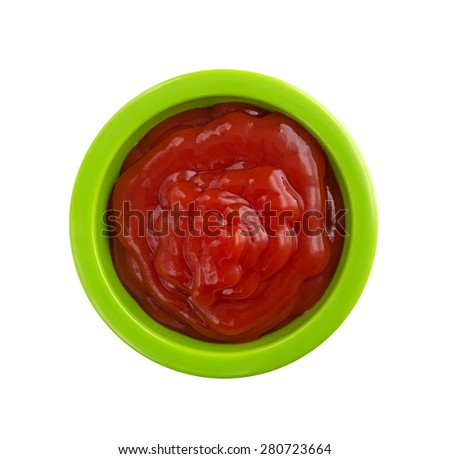 Top view of a small green portion bowl filled with ketchup isolated on a white background. - stock photo