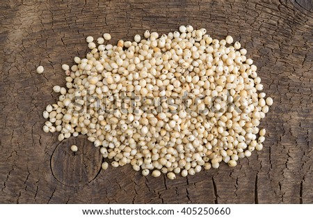 Top view of a small portion of whole grain organic sorghum seeds on an old wood board.