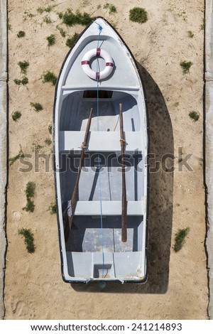 Top view of a small Portuguese traditional fishing boat  on the sand.