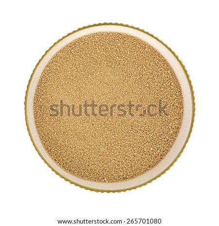 Top view of a small serving bowl with a portion of active dry yeast on a white background. - stock photo