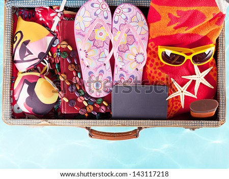 top view of a suitcase with full of summer stuff on blue background - stock photo