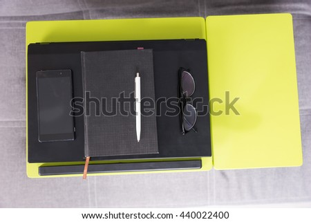Top view of a tabletop workstation with closed laptop, a diary, glasses and mobile phone are arranged in strict order on it - stock photo