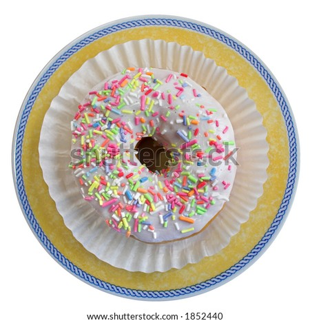 Top view of a tasty ring donut in wrapper placed on a yellow plate - stock photo