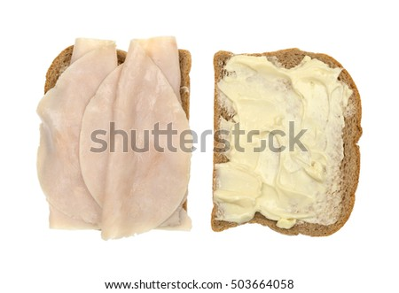 Top view of a turkey breast with mayonnaise and margarine sandwich on wheat bread open isolated on a white background.