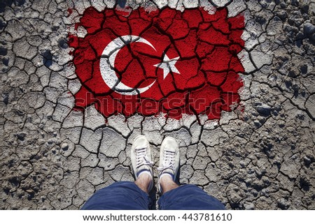 Top view of a Turkey resident standing on cracked soil with torn and cracked Turkey flag. - stock photo