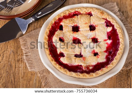 Top view of a whole cherry pie on a wooden table