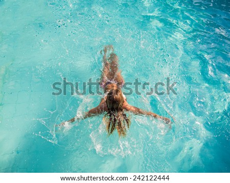 Top view of a woman in bikini at the swimming pool - stock photo
