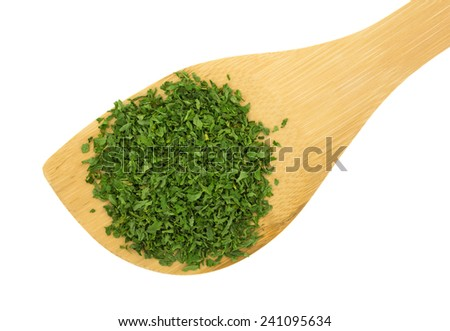 Top view of a wood spoon with dried chopped parsley flakes atop a white background. - stock photo