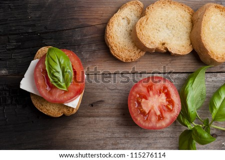 top-view of a wood table with an italian antipasto, with fresh cheese, tomato and basil - stock photo