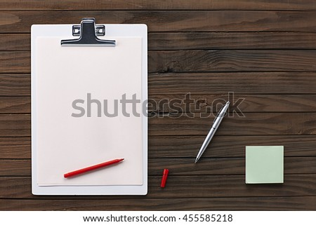 Top View of a Wooden Desk Table, White Clipboard with Blank Paper, Red Pen, Clips. Copy space for text or Image - stock photo