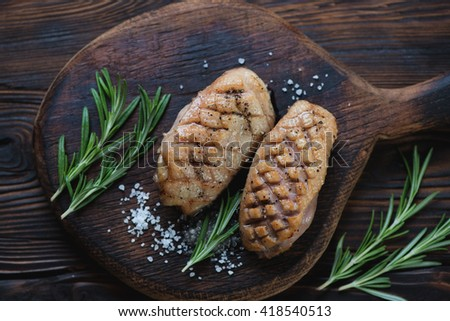 Top view of a wooden serving board with roasted duck breasts