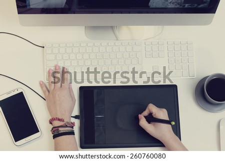 top view of a work space of a graphic designer using a graphic tablet - stock photo