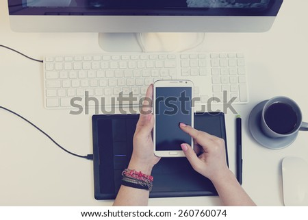 top view of a work space of a graphic designer using a smart phone - stock photo