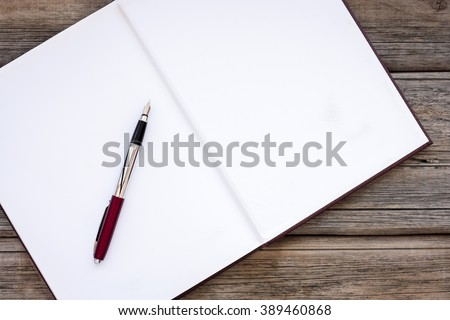 Top view of a work space with a diary and a pen - stock photo