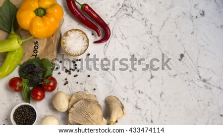 Top view of a yellow bell pepper, red chili peppers, green peppers, cherry tomatoes, basil leaves, mushrooms, black peppercorns and crushed salt on a white marble background with copy space. - stock photo