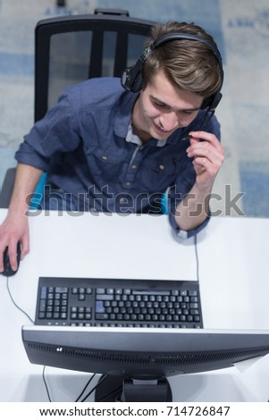top view of a young smiling male call centre operator doing his job with a headset