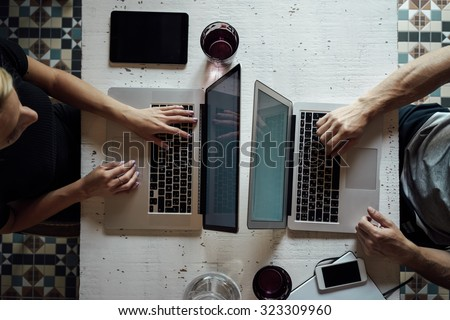 top view of a young woman and a young man who works with a laptops at the table - stock photo
