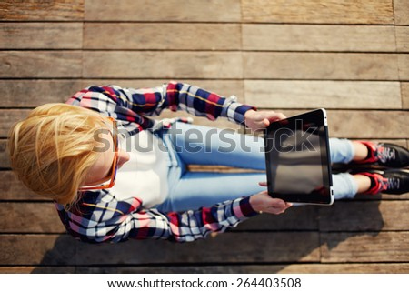 Top view of a young woman taking a picture of a view with her digital tablet while he sit on a wooden pier at sunny day, cute female tourist photographing view sitting on wooden floor outdoors - stock photo
