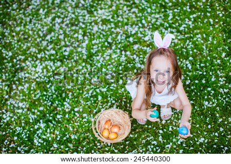 Top view of adorable little girl wearing bunny ears playing with Easter eggs on a grass covered with white flower petals on spring day - stock photo