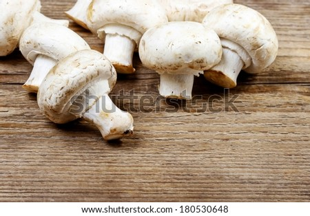 Top view of agaricus mushroom on wooden table. Copy space, blank board for your text