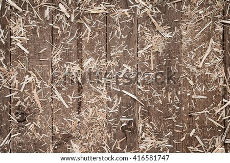 Top View of Aged, Rough textured Rustic dark Brown Cedar Wood Boards with hay scattered for Backgrounds and Templates with Blank Room or Space for your Design, Words, Text or Copy. Horizontal