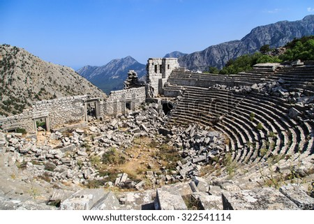 Top view of amphitheater of Termessos Antique City in Antalya, on bright blue sky background. - stock photo