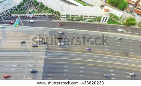 Top view of an asphalt elevated highway in Houston, Texas, US. Many passenger cars and trucks are commuting in freeway at late afternoon, warm light.Great for urban transportation publication.Panorama