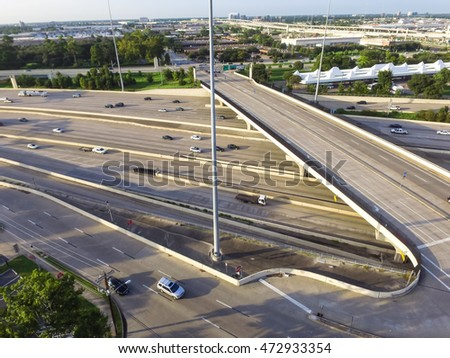 Top view of an asphalt elevated highway in Houston, Texas, US. Many passenger cars and trucks are commuting in freeway at late afternoon, warm light.Great for urban transportation publication.