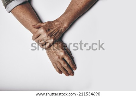 Top view of an elderly woman's hands resting on grey background. Relaxed old female hands together. - stock photo