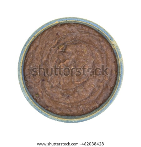 Top view of an old stoneware bowl filled with black bean dip isolated on a white background.