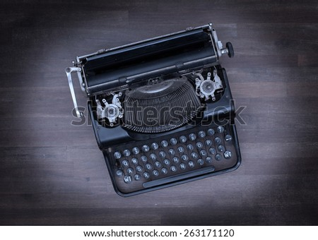 Top view of an old typewriter on a wooden table - cold blue - stock photo