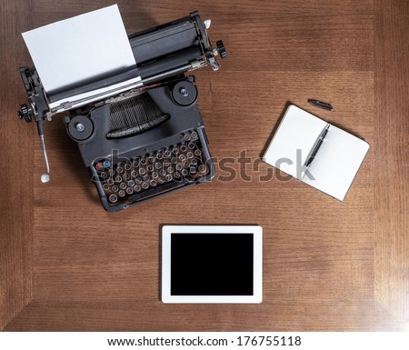 Top view of an old typewriter with a pen, a notebook and a tablet on a wooden table - stock photo