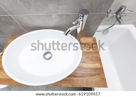 Top view of an oval porcelain sink with bath tub on the right, modern design, gray concrete tiles and chrome cylindrical tap over a wooden countertop, interior design