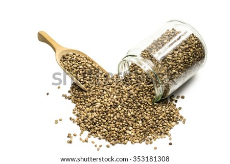 Top view of an overturned glass jar with hemp seeds and a wooden spoon on white background - stock photo