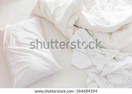 Top view of an unmade bed after waking up in the morning with a white pillow, a blanket and a shower towel on the bed. - stock photo