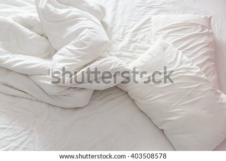 Top view of an untidy / unmade bed with white crumpled bed sheet, a blanket / duvet and two messy pillows in a hotel room. An accommodations that is not neatly arranged for a new guest to sleep in. - stock photo